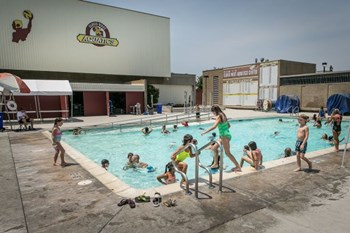 Children playing in and around a public pool