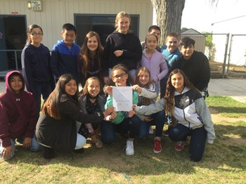 Students gathered together holding a certificate