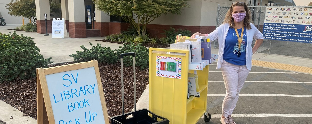 Librarian standing in the school's driveway handing out pre requested library books and collecting returned books